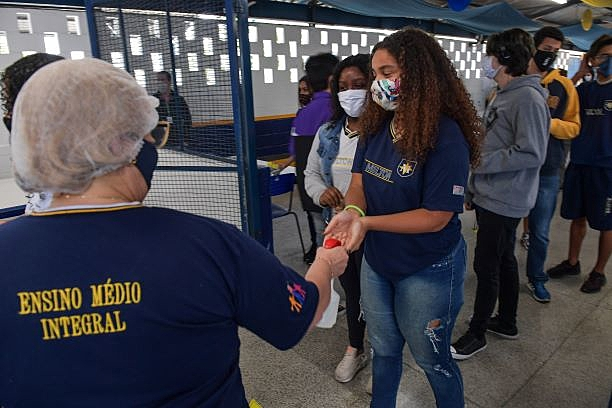 Aluna higieniza as mãos ao entrar na escola Milton da Silva Rodrigues, em São Paulo